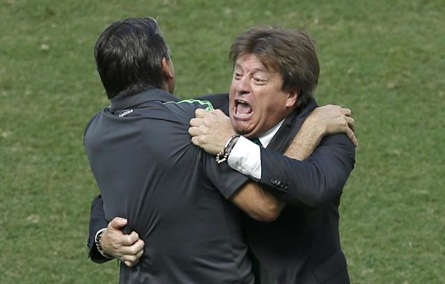 Mexico's head coach Miguel Herrera celebrates after Giovani dos Santos scored the opening goal during the World Cup round of 16 soccer match between the Netherlands and Mexico at the Arena Castelao in Fortaleza, Brazil, Sunday, June 29, 2014. (AP Photo/Themba Hadebe)
