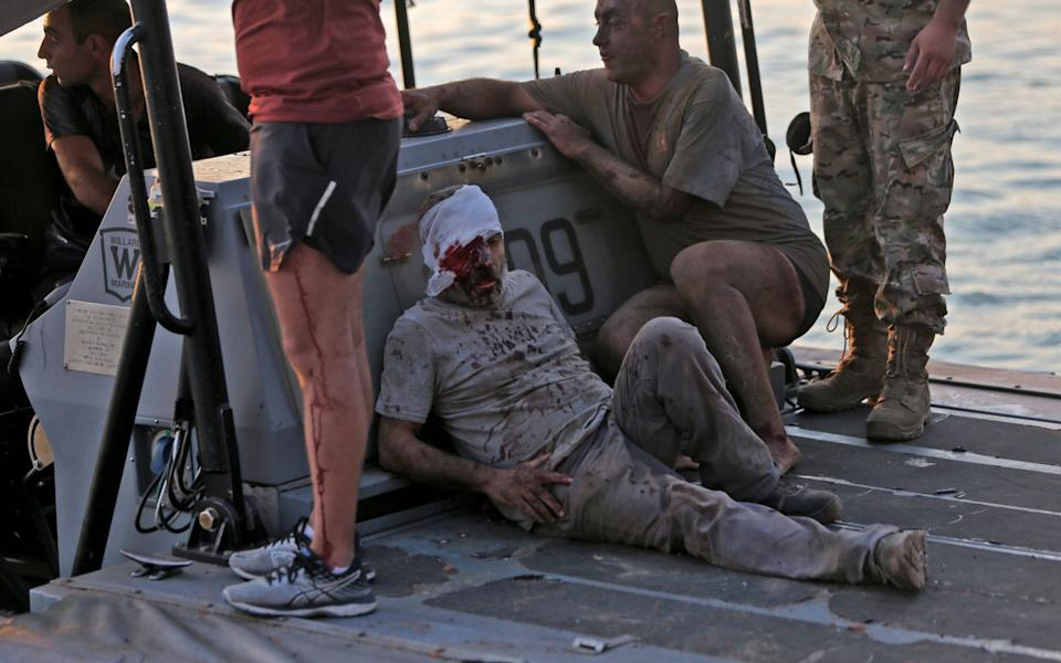 A wounded man is evacuated by boat - AFP