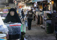 A woman street vendor waits for customers in Basra, Iraq, Wednesday, Oct. 21, 2020. Iraq is in the throes of an unprecedented liquidity crisis, as the cash-strapped state wrestles to pay public sector salaries and import essential goods while oil prices remain dangerously low. (AP Photo/Nabil al-Jurani)