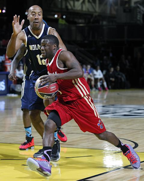 East's Bruce Bowen (12) reaches for West's Kevin Hart, foreground, in the second half as they participate in the NBA All-Star Celebrity basketball game in New Orleans, Friday, Feb. 14, 2014. East won 60-56. (AP Photo/Bill Haber)