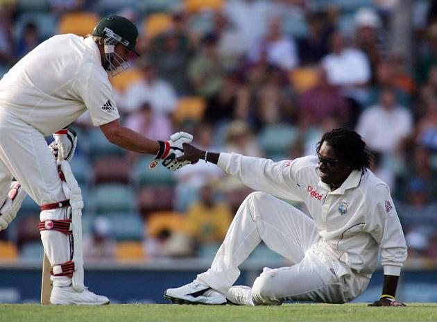 BRISBANE, QSL - NOVEMBER 3: Chris Gayle of the West Indies is helped to his feet by Shane Warne of Australia  during day one of  the 1st Test between Australia and the West Indies at the Gabba on November 3, 2005 in Brisbane, Austalia.   (Photo by Jonathan Wood/Getty Images) *** Local Caption *** Chris Gayle