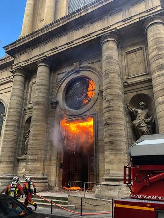 Members of the fire brigade run as a Saint-Sulpice church is seen on fire in Paris, France, March 17, 2019 in this still image taken from social media obtained on March 18, 2019.  INSTAGRAM @agneswebste/via REUTERS