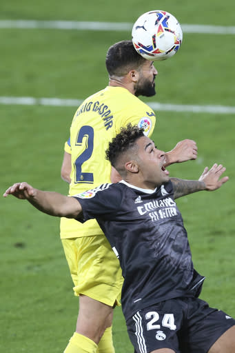 Real Madrid's Mariano Diaz, front, challenges for the ball with Villareal's Mario Gaspar during the Spanish La Liga soccer match between Villarreal and Real Madrid in Ceramica stadium in Villarreal, Spain, Saturday Nov. 21, 2020. (AP Photo/Alberto Saiz)