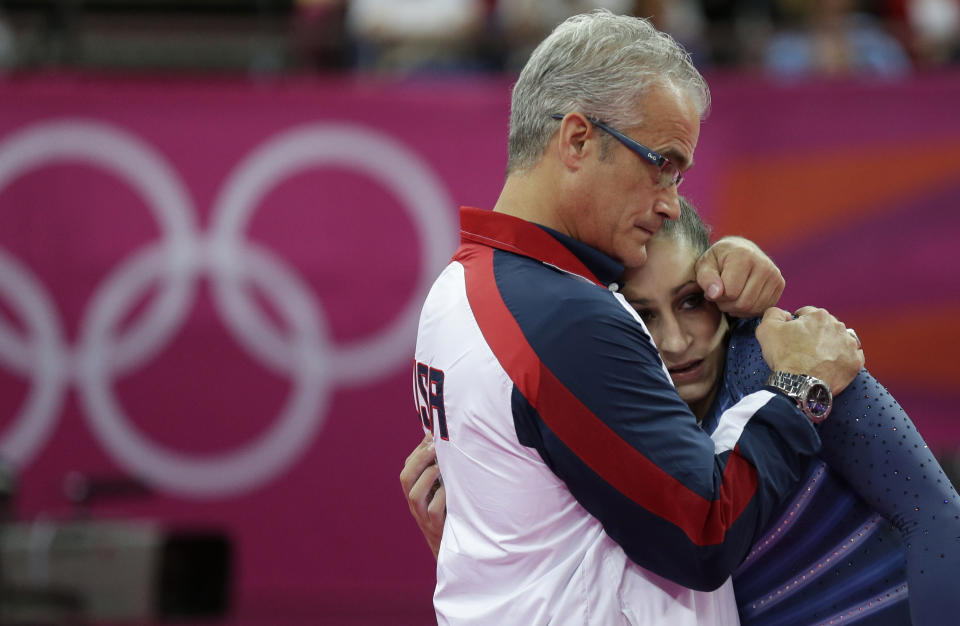 FILE - In this Aug. 7, 2012, file photo, U.S. gymnast Jordyn Wieber is consoled by head coach John Geddert after her performance during the artistic gymnastics women's floor exercise final at the 2012 Summer Olympics in London. The finality of the end of her gymnastics career hit Wieber suddenly. Too far removed from the high-intensity training needed to continue at the elite level and ineligible to compete collegiately because she turned professional as a high schooler, the 2011 world champion and 2012 Olympic gold medalist needed a place to vent.   (AP Photo/Gregory Bull, File)