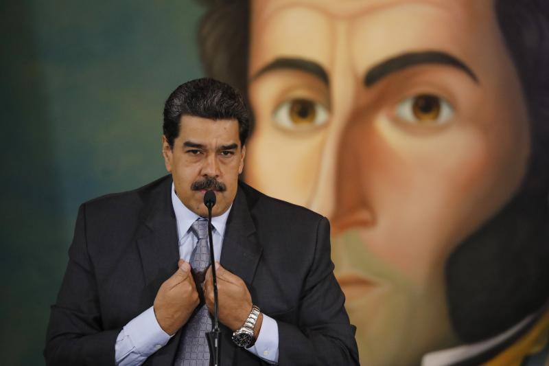 Backdropped by a painting of independence leader Simon Bolivar, Venezuela's President Nicolas Maduro gives a press conference at the Foreign Ministry in Caracas, Venezuela, Monday, Sept. 30, 2019. Maduro denied the accusation by the Colombian president that the guerrilla group ELN was operating with the Venezuelan government's support inside Venezuelan territory, answered questions about his recent trip to Russia and about a possible return to the negotiation table with the opposition. (AP Photo/Ariana Cubillos)