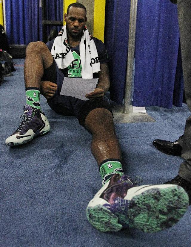 The Miami Heat's LeBron James looks at the end of game stats after the NBA All Star basketball game, Sunday, Feb. 16, 2014, in New Orleans. (AP Photo/Bill Haber)