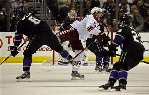 Phoenix Coyotes right winger Shane Doan (19) starts to fall after colliding with a Los Angeles Kings player in the second period of an NHL hockey game in Los Angeles Tuesday, March 19, 2013. Seen are Kings defenseman Jake Muzzin (6) and right winger Dustin Brown (23. (AP Photo/Reed Saxon)