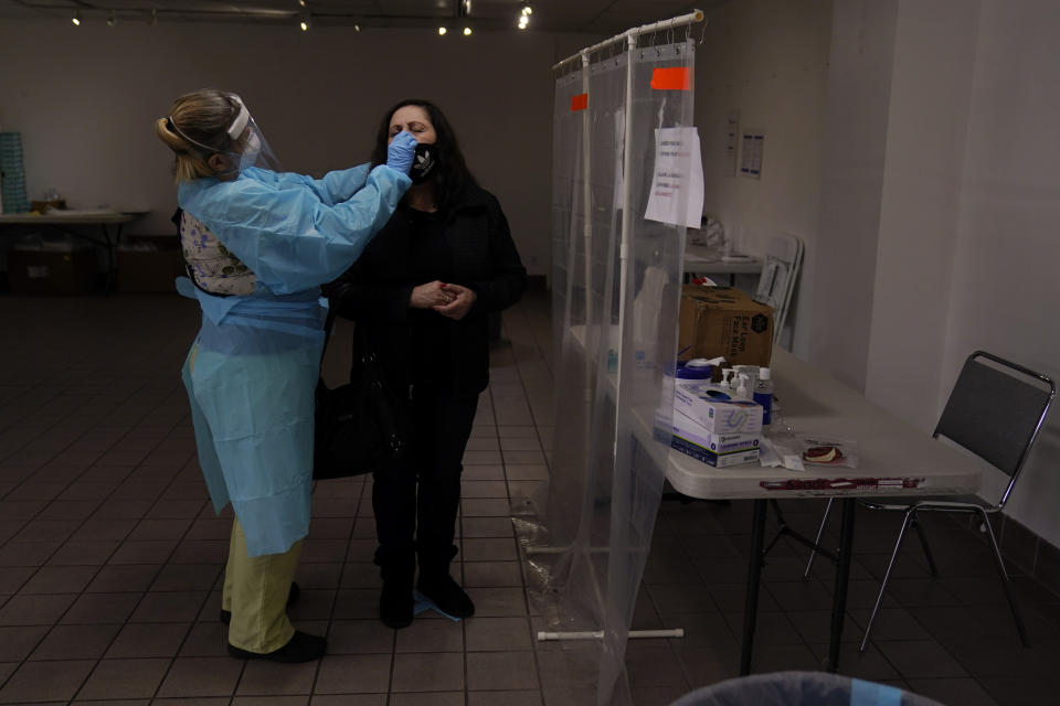 FILE - In this Dec. 27, 2020, file photo, registered nurse Leslie Clark, left, collects a nasal swab sample from a woman who declined to give her name at a COVID-19 testing site in Los Angeles. Coronavirus hospitalizations are falling across the United States, but deaths have remained stubbornly high. (AP Photo/Jae C. Hong, File)