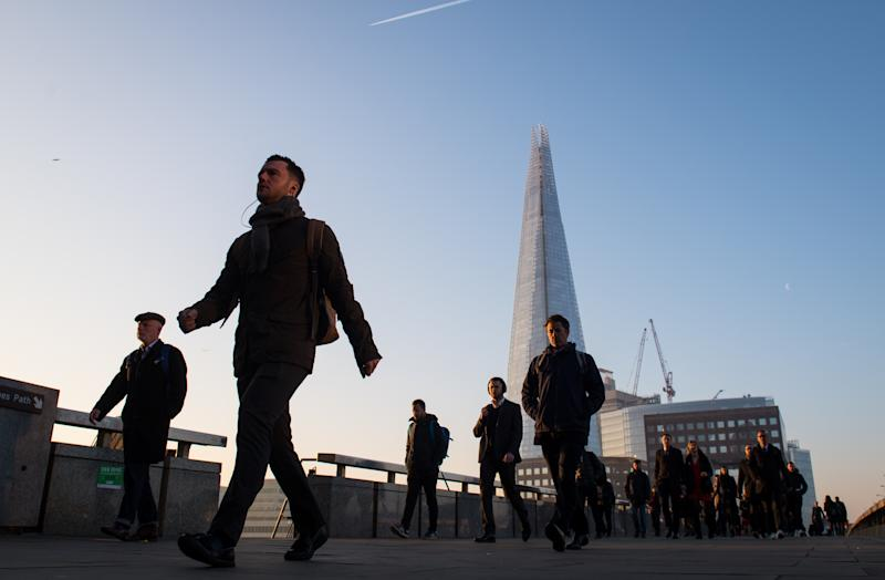 Commuters cross London Bridge, in central London, as Britain could experience more record-breaking temperatures this week. (Photo by Dominic Lipinski/PA Images via Getty Images)