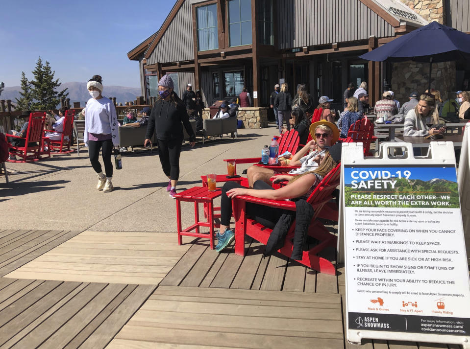 In this Oct. 3, 2020 photo, visitors to the top of Aspen Mountain eat and take in the sun in an expanded outdoor seating area in Aspen, Colo. Aspen has taken numerous precautions to prevent the spread of COVID-19 during the pandemic, including mask mandates and outdoor seating options. (AP Photo/John Marshall)
