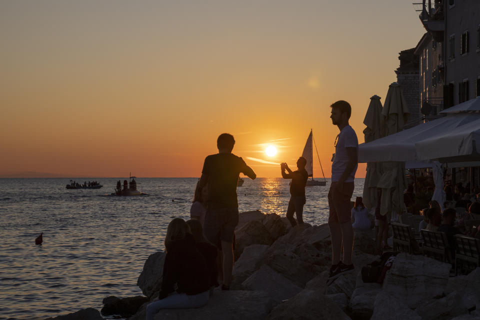 Holidaymakers enjoy the sunset on the seafront in the Adriatic town of Rovinj, Croatia, Friday, Aug. 27, 2021. Summer tourism has exceeded even the most optimistic expectations in Croatia this year. Beaches along the country's Adriatic Sea coastline are swarming with people. Guided tours are fully booked, restaurants are packed and sailboats were chartered well in advance. (AP Photo/Darko Bandic)