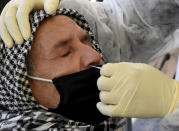 A medical technician collects a nasal swabs sample to test for COVID-19 at a mobile testing site in Tunis, Tunisia, Tuesday Dec.22, 2020. The World Health Organisation has cautioned against major alarm over a new, highly infectious variant of the coronavirus that has emerged in Britain, saying this was a normal part of a pandemic's evolution. (AP Photo/Hassene Dridi)