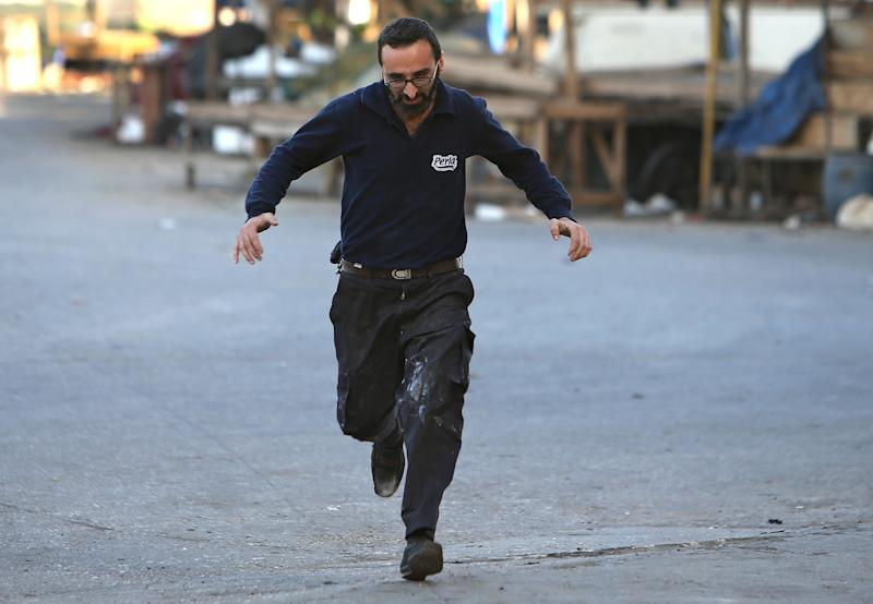 A Lebanese man runs to cross a street to avoid sniper fire, during clashes between supporters and opponents of Syrian President Bashar Assad in the northern port city of Tripoli, Lebanon, Monday, Dec. 2, 2013. Gun battles and rocket fire in the northern Lebanese city of Tripoli killed at least nine people and wounded dozens more over the weekend, the latest clash between supporters and opponents of Syrian President Bashar Assad.(AP Photo/Hussein Malla)