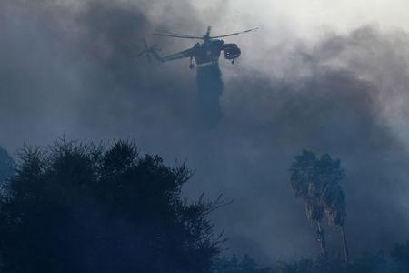 A helicopter makes a water drop on the  Lilac Fire, a fast moving wild fire in Bonsall, California, U.S., December 7, 2017.      REUTERS/Mike Blake