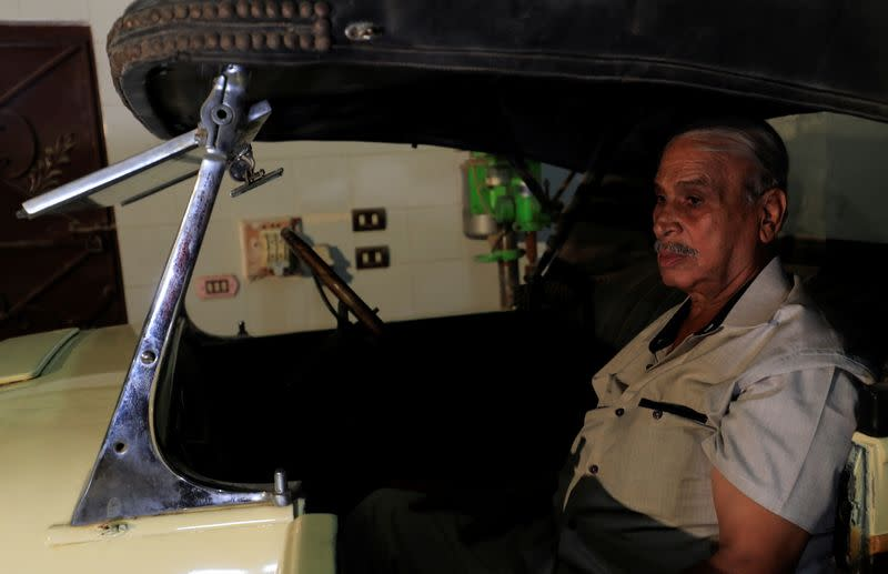 """Sayed Sima, a 70-years-old Egyptian collector of vintage cars, sits in a 120-year-old American """"1900 Auburn"""" automobile in his store, , in the Giza suburb of Abu Rawash"""