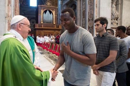Pope Francis is greeted by a migrant as he celebrates a mass for migrants to commemorate the 5th anniversary of his visit in Lampedusa, at the Saint Peter's in Vatican July 6, 2018. Vatican Media/Handout via REUTERS