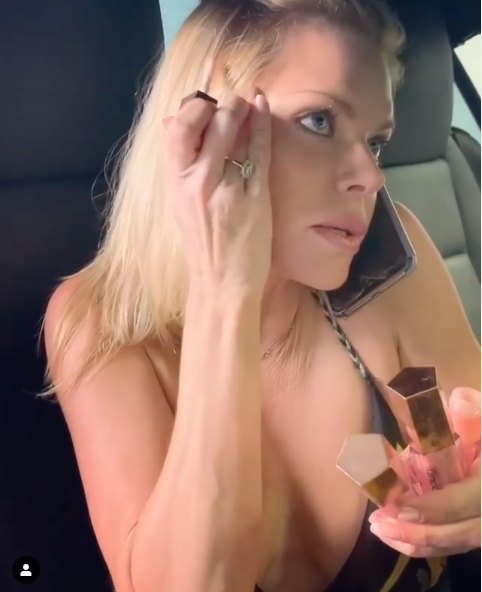 A photo of Sophie Monk applying makeup in a car.