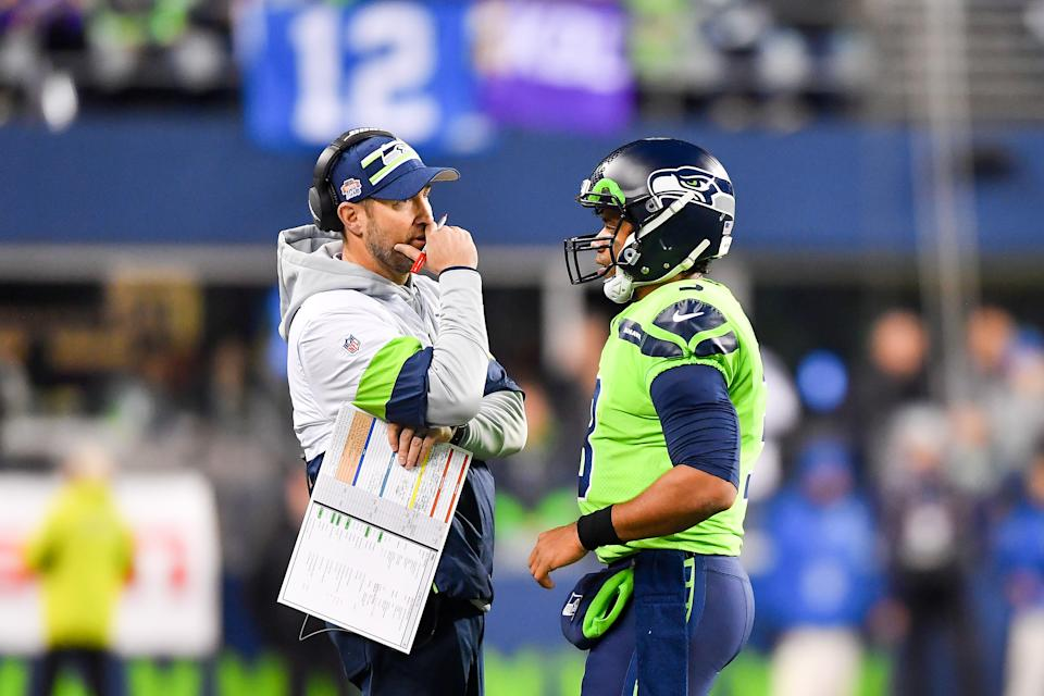 Russell Wilson chats with offensive coordinator Brian Schottenheimer during a game.