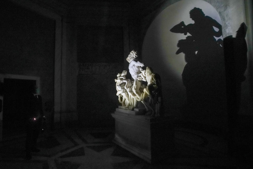 "Gianni Crea, the Vatican Museums chief ""Clavigero"" key-keeper, illuminates the Laocoon statue, a masterpiece of the sculptors of Rhodes dated around 40-30 B.C., on his way to open the museum's rooms and sections, at the Vatican, Monday, Feb. 1, 2021. Crea is the ""clavigero"" of the Vatican Museums, the chief key-keeper whose job begins each morning at 5 a.m., opening the doors and turning on the lights through 7 kilometers of one of the world's greatest collections of art and antiquities. The Associated Press followed Crea on his rounds the first day the museum reopened to the public, joining him in the underground ""bunker"" where the 2,797 keys to the Vatican treasures are kept in wall safes overnight. (AP Photo/Andrew Medichini)"
