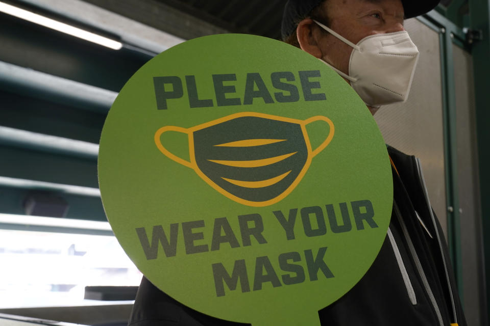FILE - In this April 3, 2021, file photo, a stadium worker holds up a sign for people to wear face masks before a baseball game between the Oakland Athletics and the Houston Astros in Oakland, Calif. California is keeping its rules for wearing facemasks in place until the state more broadly lifts its pandemic restrictions on June 15. State officials said Monday, May 17 that the delay will give people time to prepare, and for the state to make sure that virus cases stay low. (AP Photo/Jeff Chiu, File)