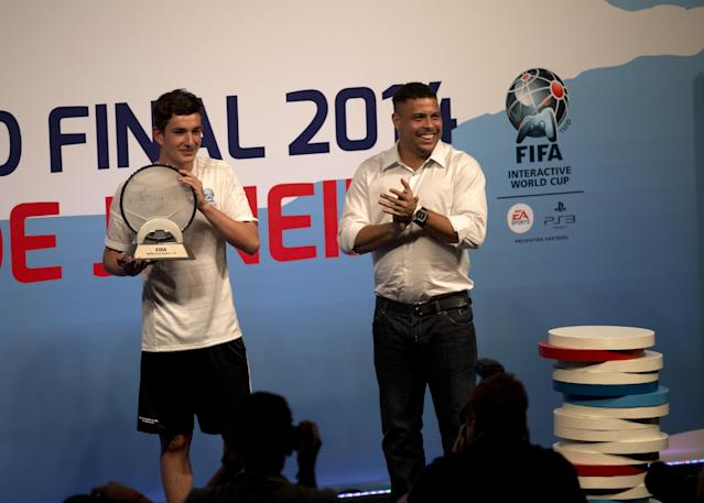 Denmark's August Rosenmeier, left, winner of the FIFA Interactive World Cup 2014, holds a trophy while Brazil's former soccer great Ronaldo applauds, during the FIFA Interactive World Cup 2014 Grand Final at Sugar Loaf, Rio de Janeiro, Brazil, Thursday, July 3, 2014. The FIWC is organized by FIFA and its presenting partners, and is recognized by Guinness World Records as the world's largest online gaming tournament. (AP Photo/Silvia Izquierdo)