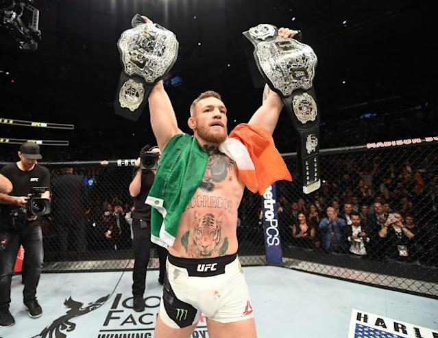 Conor McGregor, shown holding his featherweight and lightweight titles, has been interested in fighting boxer Floyd Mayweather. But on Sunday, a representative for Manny Pacquiao said Pacquiao would fight McGregor if the Mayweather bout didn't pan out. (Getty Images)