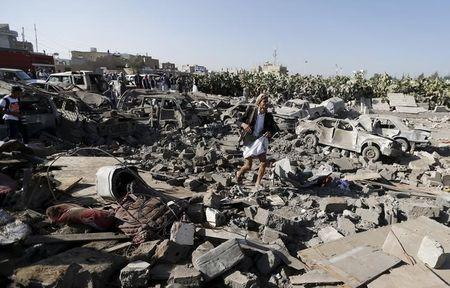 An armed man walks on the rubble of houses destroyed by an air strike near Sanaa Airport March 26, 2015. REUTERS/Khaled Abdullah