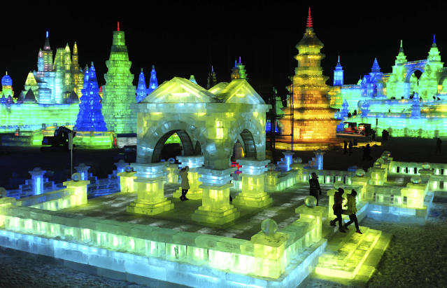 Tourists visit ice sculptures during the lights testing period of the 13th Harbin Ice and Snow World in Harbin, Heilongjiang province December 25, 2011. The Harbin International Ice and Snow Festival will be officially launched on January 5, 2012. Picture taken December 25, 2011. REUTERS/Sheng Li (CHINA - Tags: ENVIRONMENT SOCIETY TRAVEL)