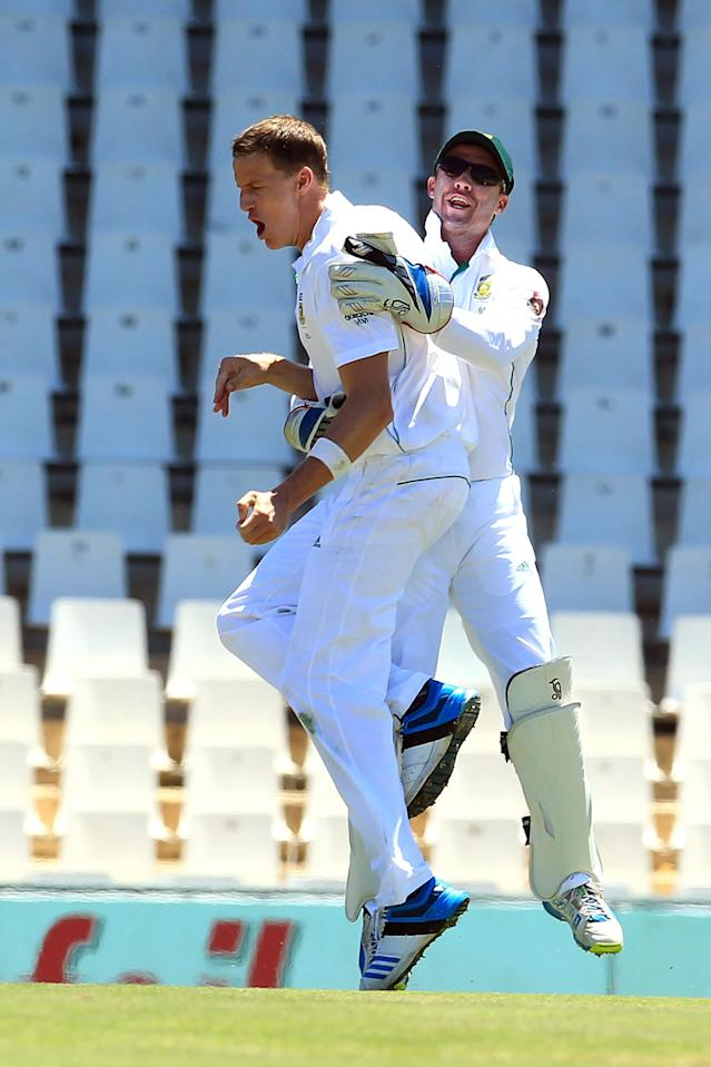 South Africa's Morne Morkel, left, celebrates with teammate AB de Villiers, right, after dismissing Australia's Chris Rogers, for 4 runs on the first day of their cricket test match at Centurion Park in Pretoria, South Africa, Wednesday, Feb. 12, 2014. (AP Photo/ Themba Hadebe)