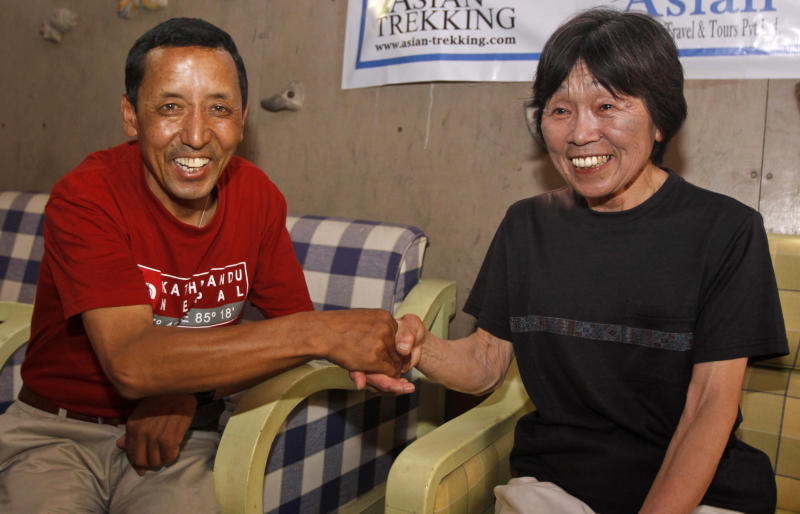Oldest woman climber of Mount Everest, Tamae Watanabe of Japan, right, is greeted by Nepal's Apa Sherpa, after arriving in Katmandu, Nepal, Friday, May 25, 2012. Watanabe, 73, has made history by becoming the oldest woman to scale the world's highest mountain, Mount Everest, bettering a record, she herself set a decade ago. (AP Photo/Binod Joshi)