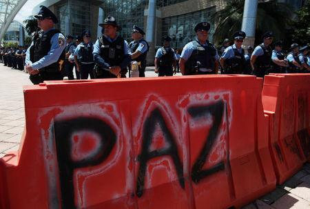 """Police stand behind a barricade, with the writing """"Peace"""" on it, to block protesters as a meeting of the Financial Oversight and Management Board for Puerto Rico is taking place at the Convention Center in San Juan, Puerto Rico March 31, 2017. Picture taken March 31, 2017. REUTERS/Alvin Baez"""