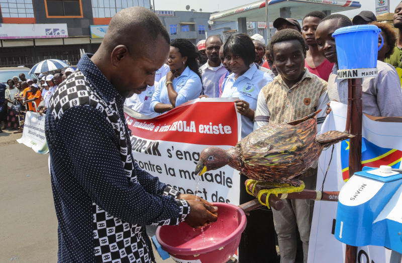 A participant washes his hands in a water dispenser shaped as a bird, during a march to raise awareness about Ebola, in the city of Goma, in eastern Congo Thursday, Aug. 22, 2019. Hundreds gathered in Goma to support Ebola response teams that have seen increasing attacks and resistance among communities where Ebola continues to spread after killing at least 1,800 people in the year since the outbreak began. (AP Photo/Justin Kabumba)