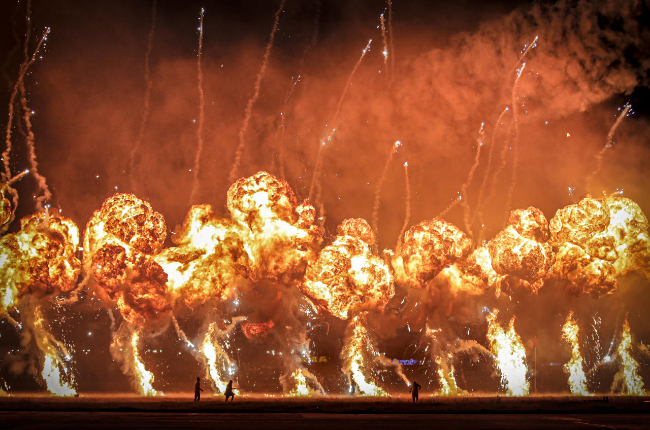 Technicians are backdropped by pyrotechnics going off during an international air show in Bucharest, Romania, Saturday Aug. 24, 2019. Thousands of Romanians took to an airfield on the edge of the capital Bucharest for a display of aerobatics and air power by pilots and aircraft from several countries. (AP Photo/Vadim Ghirda)