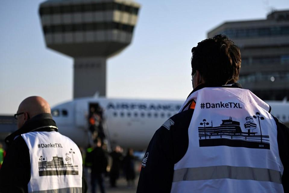 Men wear vests with the lettering 'Thank you TXL' (DankeTXL) before the departure of an aircraft of French airline Air France in Berlin on November 8, 2020.