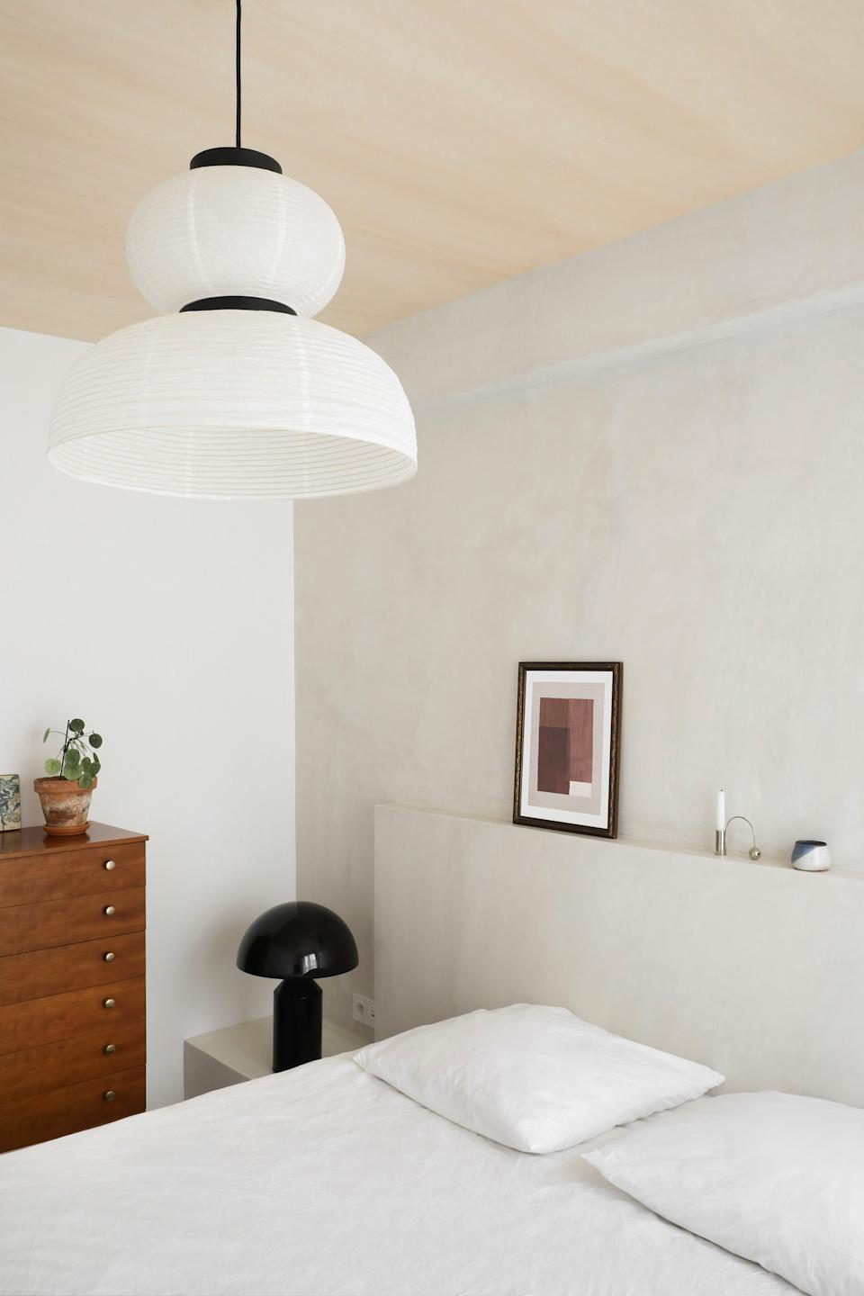 """<div class=""""caption"""">The serene primary bedroom features an Oluce lamp, a <a href=""""https://fermliving.com/products/balance-candle-holder-chrome"""" rel=""""nofollow noopener"""" target=""""_blank"""" data-ylk=""""slk:Ferm Living candleholder"""" class=""""link rapid-noclick-resp"""">Ferm Living candleholder</a>, and an <a href=""""https://www.andtradition.com/products/formakami-jh4"""" rel=""""nofollow noopener"""" target=""""_blank"""" data-ylk=""""slk:&Tradition pendant lamp"""" class=""""link rapid-noclick-resp"""">&Tradition pendant lamp</a>.</div>"""