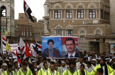 Protesters loyal to the Shi'ite Muslim Al-Houthi group, also known as Ansarullah, hold posters of Syria's President Bashar al-Assad (R) and Lebanon's Hezbollah leader Sayyed Hassan Nasrallah during a demonstration against potential strikes on the Syrian government, in Sanaa September 6, 2013. REUTERS/Khaled Abdullah