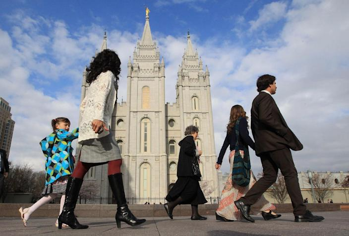 People walk pass the Salt Lake Temple on the way to the Conference Center during opening session of the two-day Mormon church conference Saturday, April 5, 2014, in Salt Lake City. More than 100,000 Latter-day Saints are expected in Salt Lake City this weekend for the church's biannual general conference. Leaders of The Church of Jesus Christ of Latter-day Saints give carefully crafted speeches aimed at providing members with guidance and inspiration in five sessions that span Saturday and Sunday. They also make announcements about church statistics, new temples or initiatives. In addition to those filling up the 21,000-seat conference center during the sessions, thousands more listen or watch around the world in 95 languages on television, radio, satellite and Internet broadcasts. (AP Photo/Rick Bowmer)