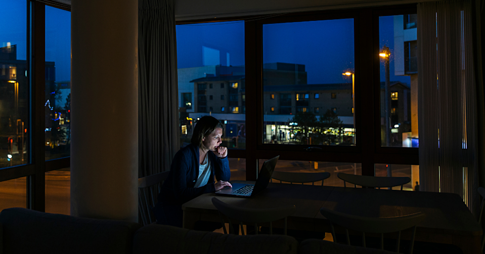 A woman works on her laptop at night.