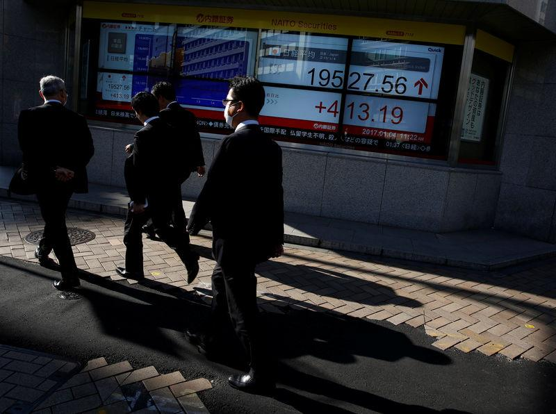 People walk past an electronic board showing stock prices outside a brokerage at a business district in Tokyo