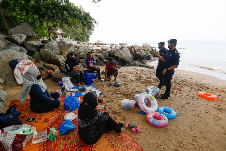 Penang CPO Datuk Mohd Suhaily Mohd Zain (left) along with North-east District Police Chief ACP Soffian Santong speak to beachgoers during the public holiday at Shamrock Beach, Batu Ferringhi, September 16, 2021. — Picture by Sayuti Zainudin