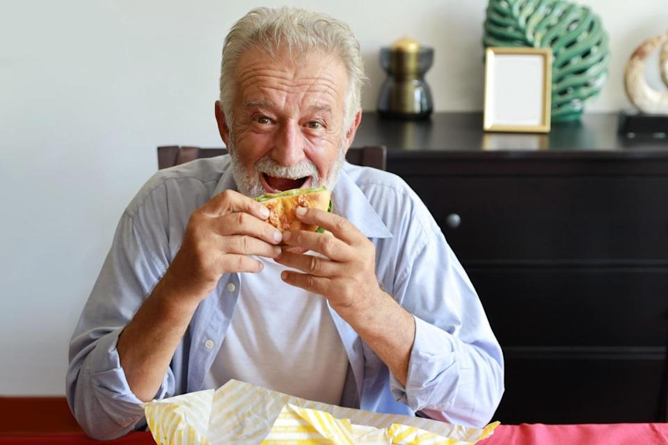Elderly man eating hamburger in living room with smiling face