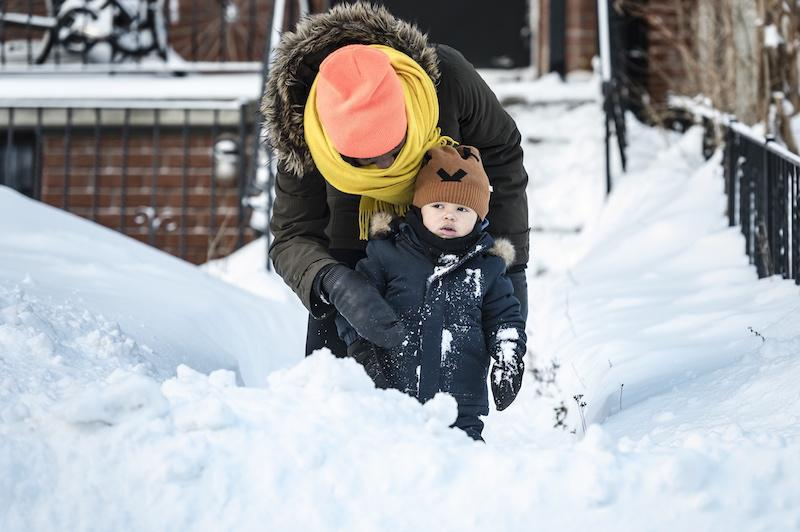 <p>Nana Yanful brushes snow off of 21-month-old Addae Yanful Paterson before going to school after a heavy winter storm in Toronto on Jan. 29, 2019. Photo from The Canadian Press. </p>