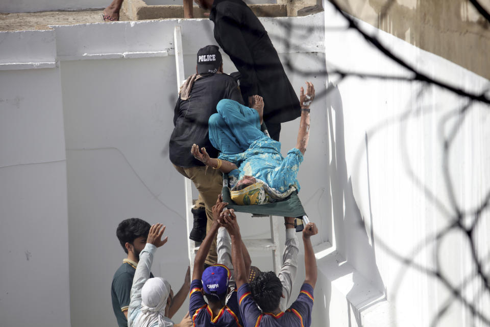 Volunteers carry an injured person at the site of a plane crash in Karachi, Pakistan, Friday, May 22, 2020. An aviation official says a passenger plane belonging to state-run Pakistan International Airlines carrying more than 100 passengers and crew has crashed near the southern port city of Karachi. (AP Photo/Fareed Khan)