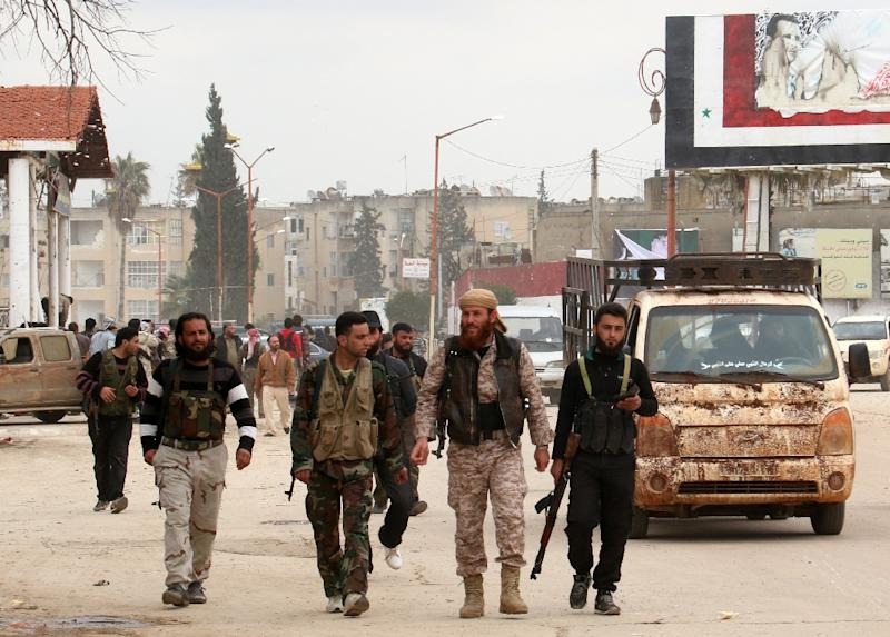 Fighters from a coalition of Islamist forces walk on March 29, 2015 in the Syrian city of Idlib, the second provincial capital to fall from government control