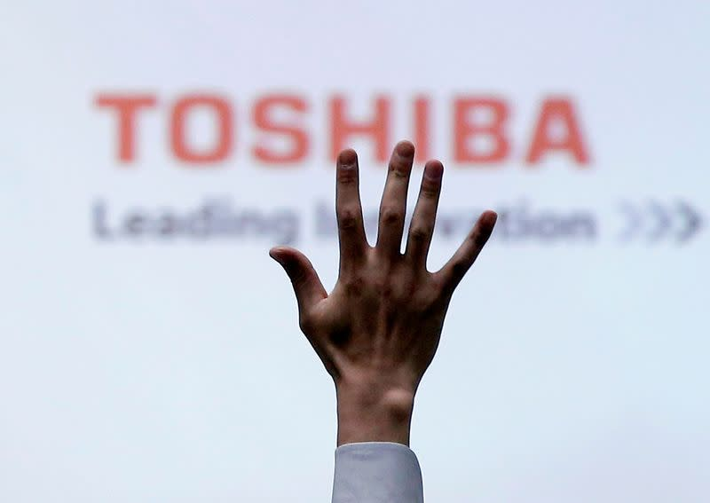 FILE PHOTO: A reporter raises his hand for a question during a news conference by Toshiba Corp CEO Satoshi Tsunakawa at the company headquarters in Tokyo