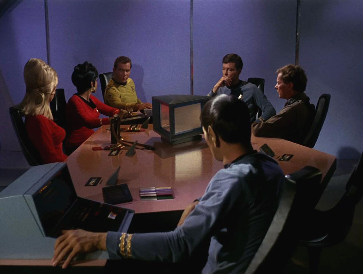 The crew of the Starship Enterprise sit around a table in a scene from 'The Man Trap,' the premiere episode of 'Star Trek,' which aired on September 8, 1966. Clockwise from left are American actress Grace Lee Whitney as Yeoman Rand, American actress Nichelle Nichols as Uhura, Canadian actor William Shatner as Captain James T. Kirk, American actor DeForest Kelley (1920 - 1999) as Dr. Leonard 'Bones' McCoy, American actor Alfred Ryder (1916 - 1995) as Professor Robert Crater and American actor Leonard Nimoy as Mr. Spock. (Photo by CBS Photo Archive/Getty Images)