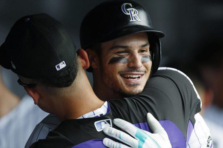 Nolan Arenado (right) gets a hug from Carlos Gonzalez after hitting one of his three home runs in Wednesday's 18-4 win against the Padres. (AP)