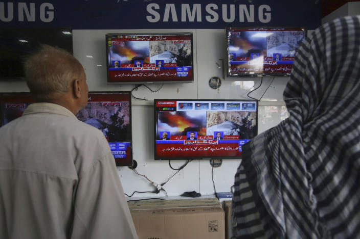 Pakistani watch news bulletins on television in Karachi, Pakistan, Wednesday, Feb. 27, 2019. Pakistan's air force shot down two Indian warplanes after they crossed the boundary between the two nuclear-armed rivals in the disputed territory of Kashmir on Wednesday and captured one Indian pilot, a military spokesman said. (AP Photo/Fareed Khan)