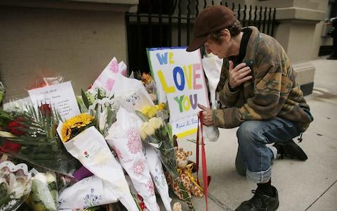 Flowers are laid in front of the Krim family's Upper West Side apartment - Credit: Getty/Spencer Platt