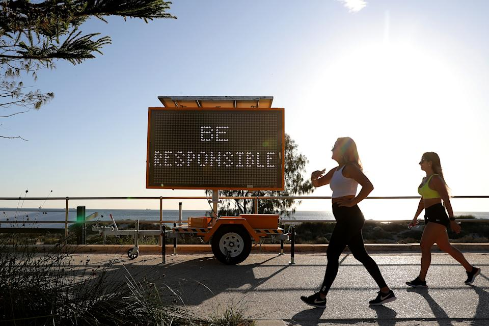 Two women walk past a sign at Scarborough Beach, Perth. Source: AAP